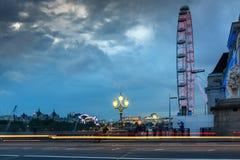 伦敦,英国- 2016年6月16日:伦敦眼和从威斯敏斯特桥梁,伦敦,英国的县政厅的夜照片 免版税图库摄影