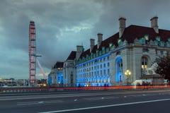 伦敦,英国- 2016年6月16日:伦敦眼和从威斯敏斯特桥梁,伦敦,英国的县政厅的夜照片 免版税库存照片