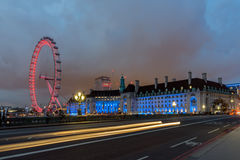 伦敦,英国- 2016年6月16日:伦敦眼和从威斯敏斯特桥梁,伦敦,英国的县政厅的夜照片 库存图片