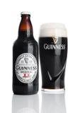 伦敦,英国- 2016年11月29日:吉尼斯额外壮健啤酒瓶和玻璃在白色背景 吉尼斯啤酒是导致的s 免版税库存照片