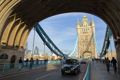 伦敦,英国- 2016年1月16日:在塔桥梁的一辆黑出租汽车用嫩黄瓜在背景中 库存图片