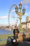 伦敦,英国- 2015年12月31日:弹风笛的苏格兰音乐家在威斯敏斯特桥梁的日落有在backgrou的伦敦眼的 库存照片