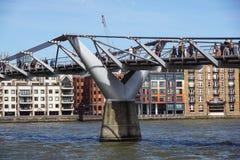 伦敦,英国- 2015年5月13日:游人和通勤者在有圣的Pauls千年桥梁走在a的背景中 免版税图库摄影