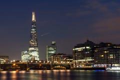 伦敦,英国- 2016年6月17日:Southwark桥梁、碎片摩天大楼和泰晤士河,伦敦夜全景  免版税库存图片