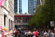 伦敦,英国- 2014年4月13日-在金丝雀码头唱腔的伦敦马拉松,专家的巨型的体育比赛和爱好者运动员, 免版税库存图片