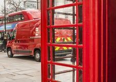 伦敦-一辆红色皇家邮车、一辆红色公共汽车和一个红色电话亭街道  免版税库存照片