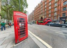 伦敦- 2016年9月:在一个红色电话亭附近的城市交通 Lo 免版税图库摄影