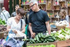 伦敦- 2015年6月12日:未认出的人民在2015年6月12日的伦敦在自治市镇市场上购买菜 库存照片