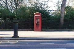 伦敦- 3月30 :偶象电话亭在公园前面的肯辛顿庭院里有2017年3月30日的篱芭的 免版税库存照片