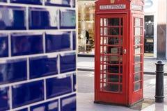 伦敦- 3月30 :有蓝色瓦片墙壁的偶象电话亭2017年3月30日 免版税库存图片
