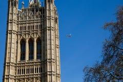 伦敦- 4月14 :飞行飞机的酋长管辖区航空公司在大本钟附近在议会议院在伦敦 免版税库存照片