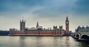 伦敦/英国- 02 07 2017年:议会大厦在与威斯敏斯特桥梁的多云晚上在右边 免版税库存图片