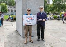伦敦/英国- 2019年6月26日-夫妇在议会正方形运载时期是现在签字,作为时期一部分现在是气候变化事件 库存照片