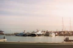 巴伦西亚,西班牙- 2016年2月03日:在巴伦西亚,有大量的码头港的晚上游艇和日落与桃红色天空 免版税图库摄影