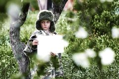 伪装制服和一个帽子的男孩有earflaps立场的在有干净的白色板料的一棵苹果树 免版税库存图片