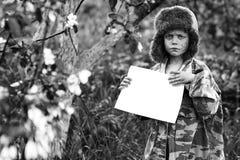 伪装制服和一个帽子的男孩有earflaps立场的在有干净的白色板料的一棵苹果树 库存照片