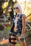 伪装和步枪的美丽的妇女 免版税库存图片