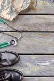 伪装夹克、听诊器和黑发光的鞋子 免版税库存照片