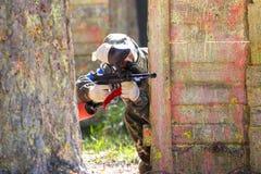 伪装射击的人从迷彩漆弹运动枪 库存照片