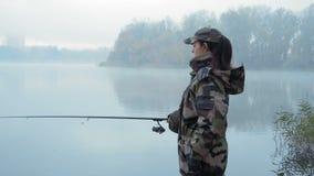 伪装服装的美丽的女渔翁女孩投掷钓鱼竿入河在有雾的秋天早晨 股票视频