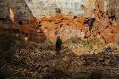伪装的人与背包沿城市废墟走 岗位启示概念 库存图片