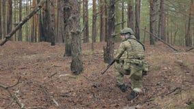 伪装的战士与作战武器做他们的方式森林外,打算夺取它,军事 影视素材
