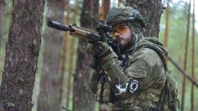 伪装的战士与作战武器在森林的风雨棚,军事概念被解雇 股票录像