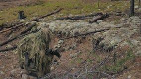 伪装的战士与作战武器在森林的风雨棚,军事概念被解雇 影视素材