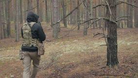 伪装的战士与作战武器在森林的风雨棚,军事概念被解雇 股票视频
