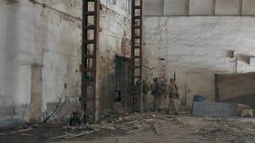伪装的战士与作战武器沿老大厦偷偷地走,军事概念的走廊 股票视频