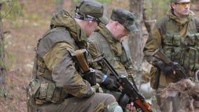伪装的战士与军用武器在森林的风雨棚,军事概念休息
