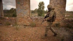 伪装的走的战士横渡与自动炮的被放弃的砖瓦房外部在他的胳膊,确信和 影视素材