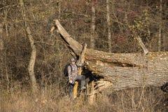 伪装衣服的一个人在一棵老橡木旁边 免版税库存图片