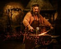 伪造在铁砧的资深铁匠熔融金属在铁匠铺 免版税库存图片
