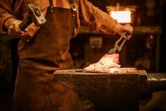 伪造在铁砧的资深铁匠熔融金属在铁匠铺 库存照片