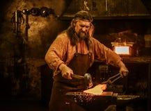 伪造在铁砧的资深铁匠熔融金属在铁匠铺 库存图片
