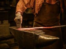 伪造在铁砧的资深铁匠熔融金属在铁匠铺 免版税库存照片