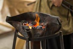 伪造垫铁的橙色火煤炭在一种透雕细工金属滚保龄球 免版税库存照片