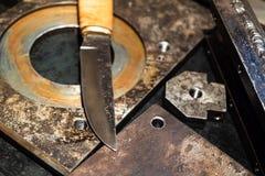 伪造的刀子关闭刀片在金属工作凳 免版税库存图片