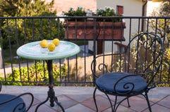 伪造的桌和椅子与蓝色枕头在大阳台俯视公园的晴朗的夏日 免版税库存图片