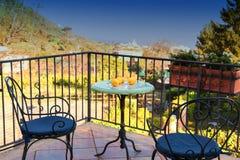 伪造的桌和椅子与蓝色枕头在大阳台俯视城市和海的晴朗的夏日 免版税库存照片