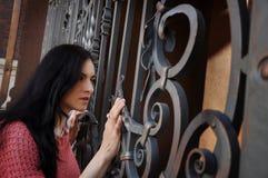 伪造的篱芭背景的美丽的深色的女孩  免版税库存照片