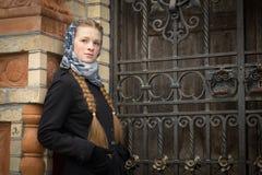 伪造的门的美丽的红发女孩 免版税图库摄影