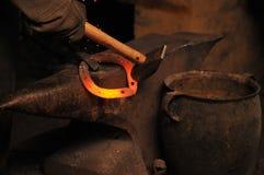 伪造马掌的铁匠由锤子 免版税图库摄影