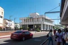 伯利兹- 2017年11月17日:与当地人民和交通的伯利兹市都市风景 伯利兹银行在背景中 免版税库存图片