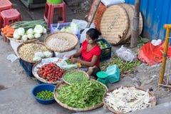伯曼妇女出售蔬菜和水果在街道食物市场上在仰光,缅甸 库存图片