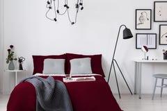 伯根地卧具和灰色枕头在一张床上在白色墙壁卧室内部 实际照片 免版税图库摄影