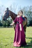 伯根地礼服的一个美丽的女孩拿着一匹棕色马 免版税库存图片