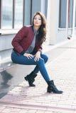 伯根地飞行员` s夹克的年轻美丽的时髦的妇女和蓝色牛仔裤,街道样式、春天和秋天趋向,看,在t的头发 免版税库存图片