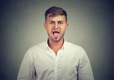 伸出他的舌头的一个人的画象  免版税库存图片
